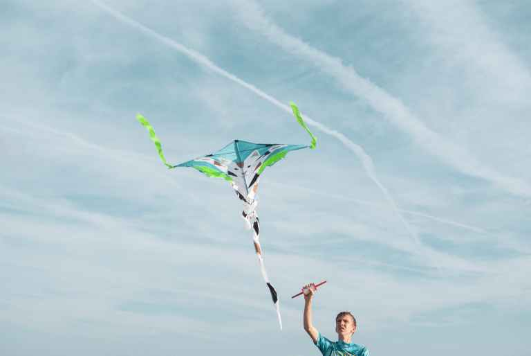 man wearing blue shirt flying kite